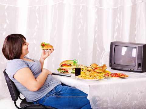 A lady affected by the pandemic disease of obesity eating a lot in front of the TV set