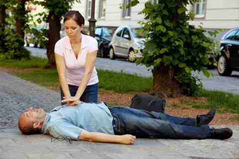 A man is having a heart attack in the street, attended by a young lady