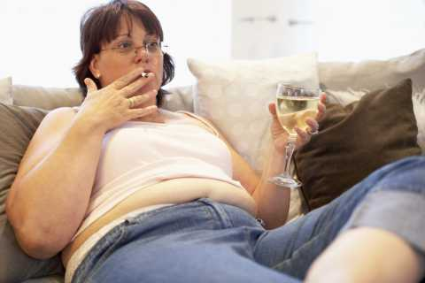 An overweight woman watching tv