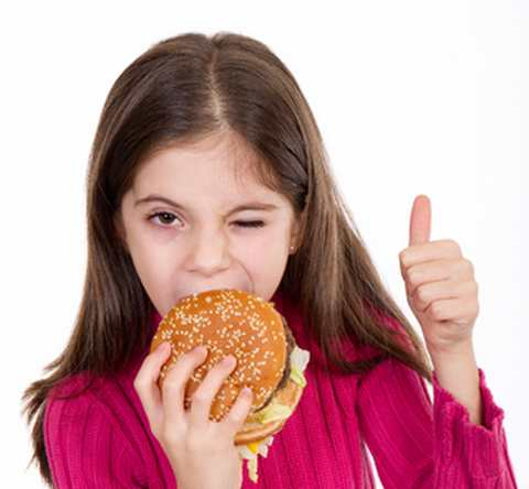 An adorable girl eating a hamburger